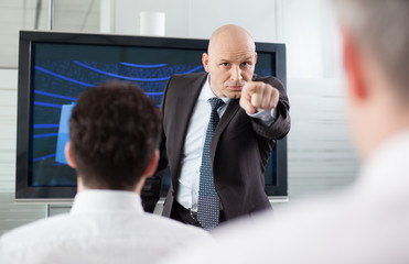 Angry boss pointing his finger at his employee during a meeting.
