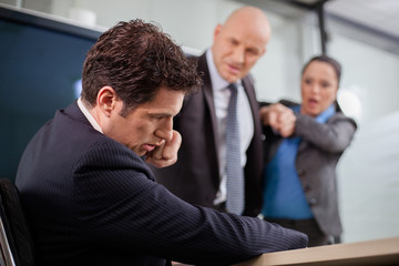 Businessman punching his colleague in the face at a meeting