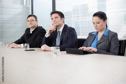 Business people at a meeting, listening to their superior
