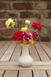 Carnations and celandines in white vase on garden table