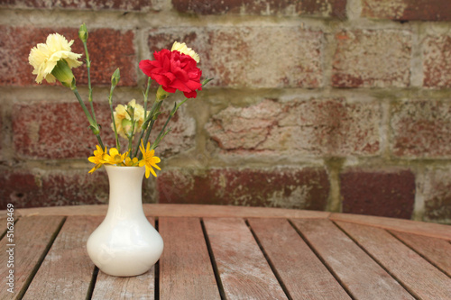 Flowers in little white vase on garden table
