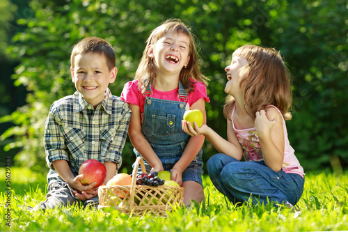 Three happy smiling child playing in park - 51629233