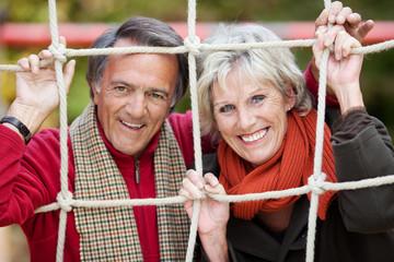 lachendes älteres paar schaut durch kletternetz