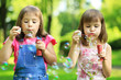 Two little girl blowing soap bubbles in the parc