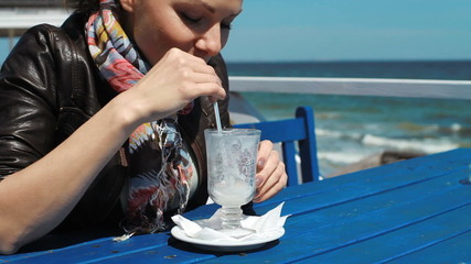 young beautiful girl is drinking a cocktail on the beach cafe