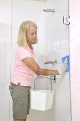 Frau putzt Fliesen in der Dusche