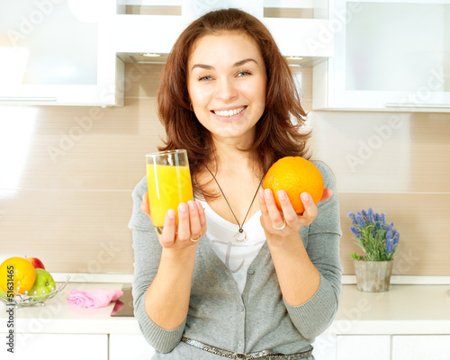 Healthy Girl with Orange Juice in the Kitchen