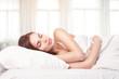 Beautiful woman lying down in bed
