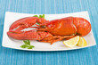 Lobster and lemon wedges on a blue background.