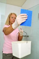 Frau putzt die  Dusche mit Putzlappen