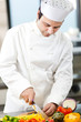 Young chef cutting vegetables in a kitchen