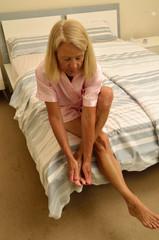Seniorin sitzt auf einem Bett und massiert ihre Füsse