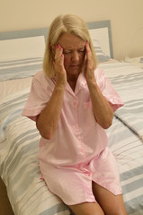 Seniorin sitzt auf einem Bett mit Depressionen
