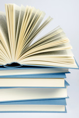 A stack of blue books on light blue background