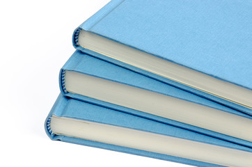A fan of three blue books on a white background