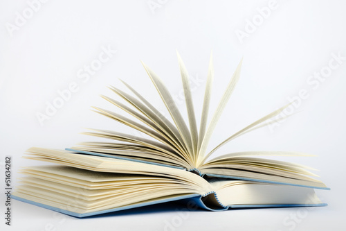 Two open blue books on a light blue background