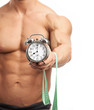 Cropped view of muscular man holding clock and measuring tape