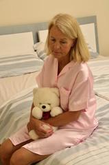 Seniorin sitzt auf einem Bett mit Teddybär