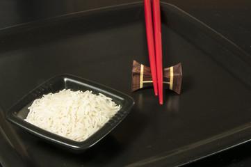 Sushi Reis mit roten Stäbchen auf schwarzem Teller