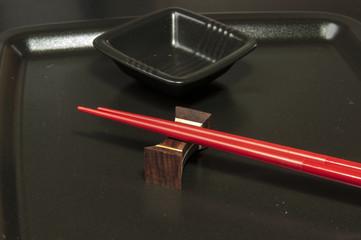Sushi Besteck mit schwarzem Teller und roten Stäbchen