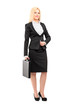 Full length portrait of a blond businesswoman holding a suitcase