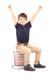 A happy school boy raised his hands gesturing happiness, seated