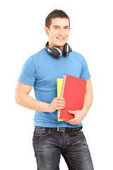 A handsome student with headphones holding books