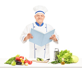 A mature chef reading a cookbook during a preparation of salad