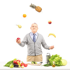 A smiling mature man juggling fruits behind a table full with in