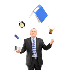 Mature man in a suit juggling with office supplies
