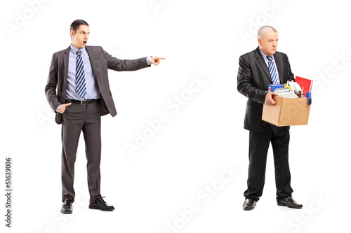Full length portrait of an angry boss firing an employee