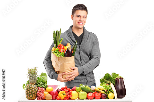 Handsome young man with a bag of groceries standing behind a pil