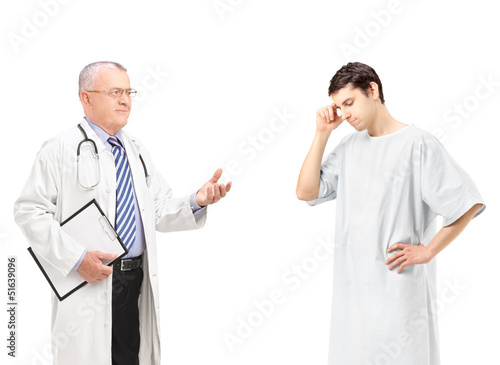 Mature doctor talking to a worried male patient