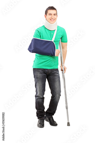 Full length portrait of a smiling male with broken arm and crutc