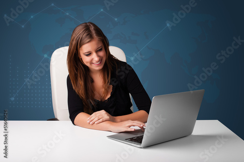 Young woman sitting at desk and typing on laptop