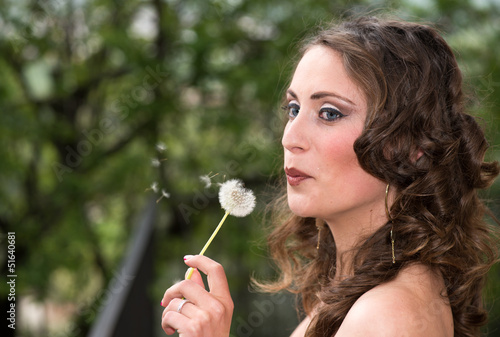 Beautiful young woman blowing on a Taraxacum Flower