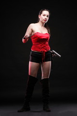 Sexy young woman - gun on black background