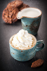 Сup of coffee with whipped cream and chocolate cookies