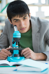 Male student in laboratory looking at camera while working with
