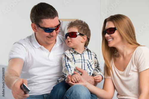 Family laughing while watching television together in the living