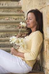 Attractive mature woman in love with flower