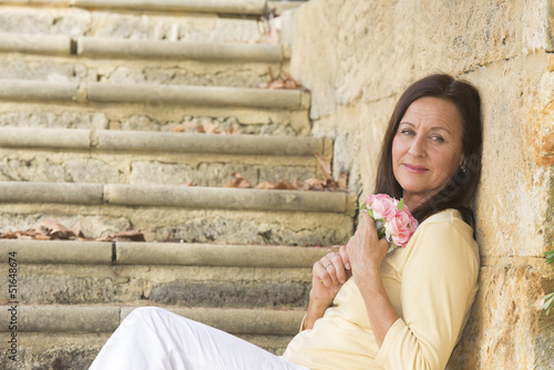 Attractive mature woman in love with rose