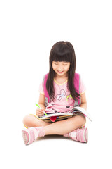 happy asian little girl sitting and reading a book