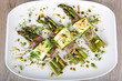 Delicious bunch of asparagus rolled with ham, zucchini, pine nut