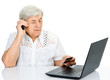 old woman using laptop, talking on cell phone. isolated