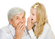 girl telling an astonished old woman some secrets. isolated