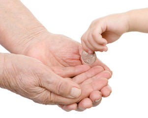 hands of the child put a coin in a palm of the old person.