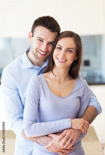 Young couple hugging at home