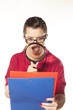 Surprised pretty woman looking at folders with magnifying glass