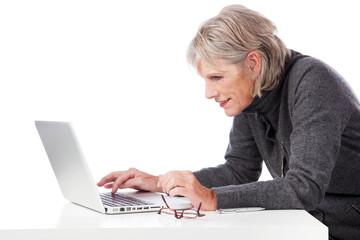 seniorin schaut konzentriert auf laptop